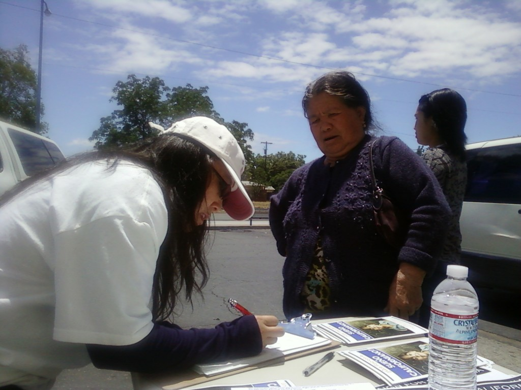 Molly Xiong assists a new citizen in becoming a registered voter.
